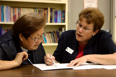 A tutor helps an adult learn to read
