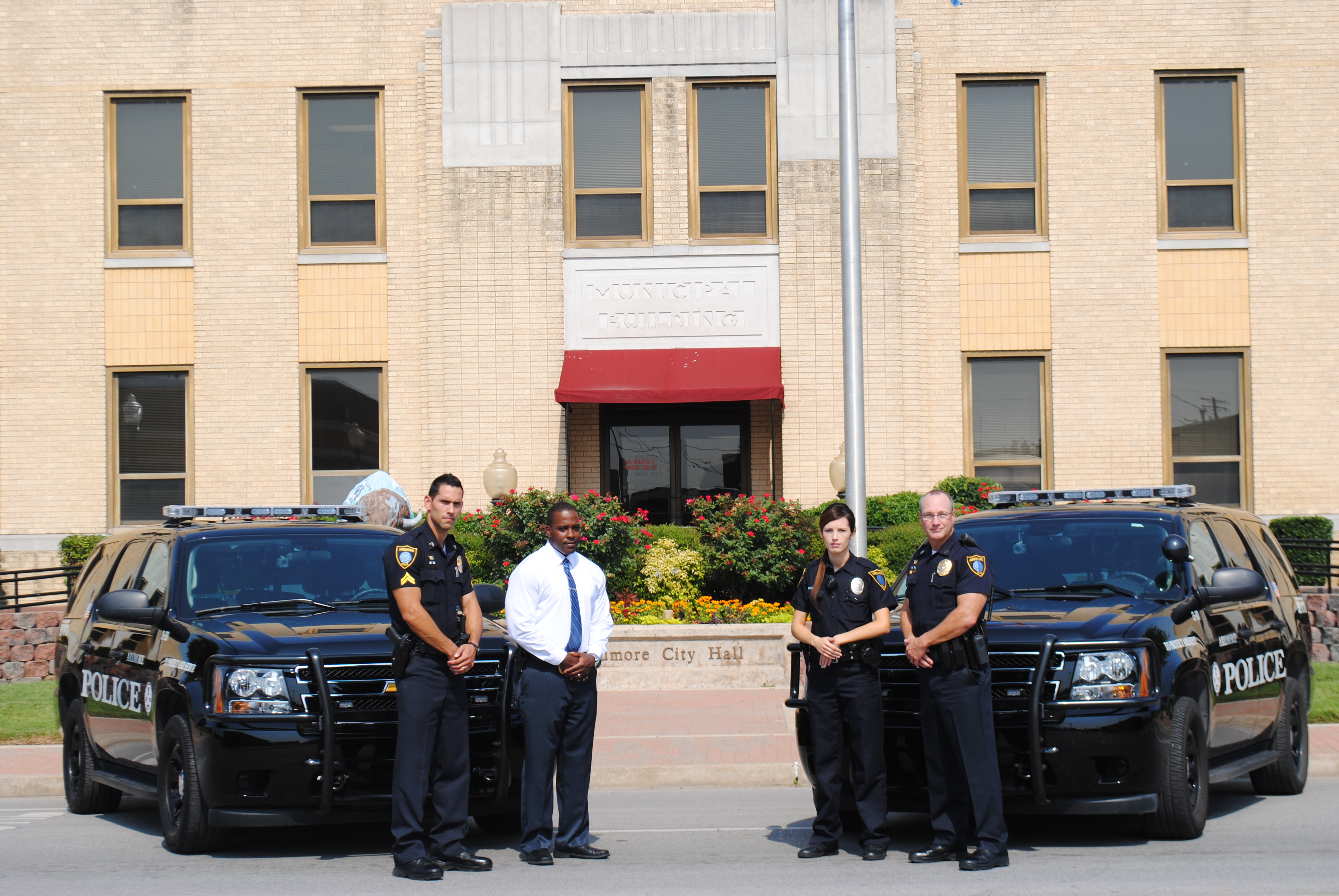 photo of four officers and two police units in front of city hall